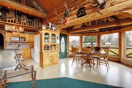 View of kitchen room and dining area in log cabin house. Furnished with wooden cabinets, rustic dining table set photo
