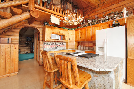 Bright kitchen room with rocky counter cabinet, rustic counter stools, horn chandelier. Log cabin house interior photo