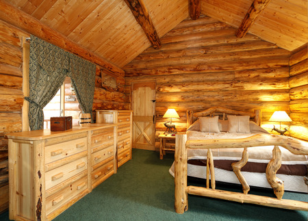 Warm cozy bedroom with rustic bed, nightstand and dresser. Green carpet floor and curtains. Log cabin house interior photo