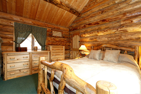 nightstand: Warm cozy bedroom with rustic bed, nightstand and dresser. Green carpet floor and curtains. Log cabin house interior