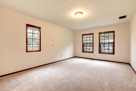 beige: View of the empty room with beige carpet floor and windows Stock Photo