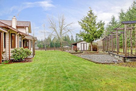 Farm house backyard wigh a lawn, trees and wooden grids. View of the fenced horse barn Stock Photo - 26300741