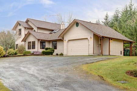 curb appeal: Siding farm house with attached car garage. View of the house from a drive way