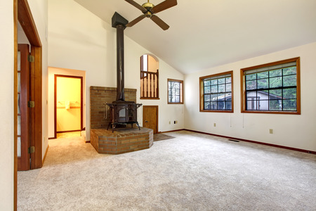 Farm house living room with vaulted ceiling and carpet floor. Brick base with an antique stove on it. photo