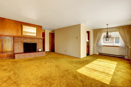 Empty bright living room with carpet floor, brick background fireplace and built-in cabinet