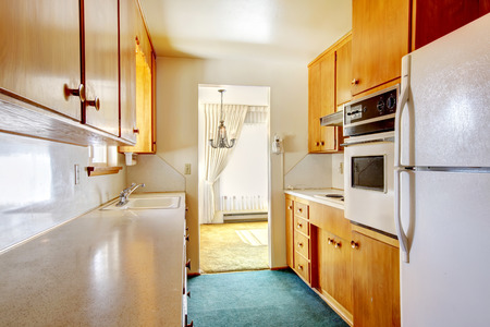 Small kitchen room with blue carpet floor, white appliances and wooden cabinets photo