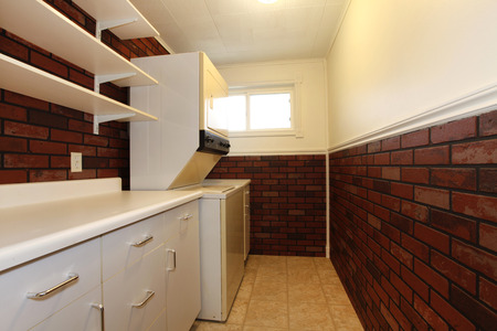 Great wall design with brick facing in the laundry room. Furnished with whtie cabinets, wall shelves, washer and dryer
