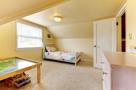 bedroom furniture: Yellow vaulted ceiling room with carpet floor. Furnished with wooden bed, table and dresser