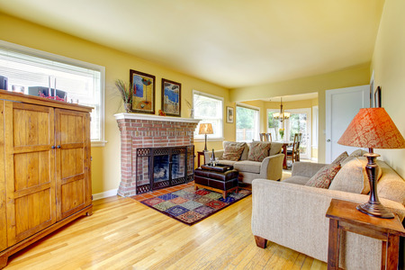 Yellow tones living room with hardwood floor and brick background fireplace. photo