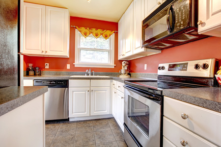 counter top: Small kitchen room with concrete tile floor, red walls, steel appliances and white wooden cabinets