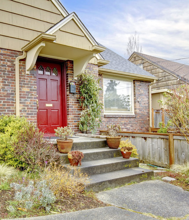 curb appeal: Tile roof brick house with red door. Stairs decorated with flower pots