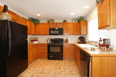 black appliances: Bright kitchen room with tile floor. Furnished with brown wooden cabinets and black modern appliances