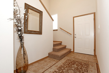 Light wall entrance hall with a rug. Decorated with a mirror and vase with dry branches photo