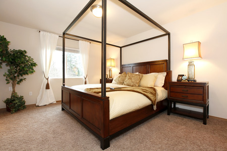 nightstands: Light tones bedroom with a brown carpet floor. Furnished with a queen size bed with high posts, nightstands. Decorated with a green tree.