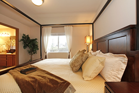 nightstands: Light tones bedroom. Furnished with a queen size bed with high posts, nightstands. Decorated with a green tree. View of the bathroom