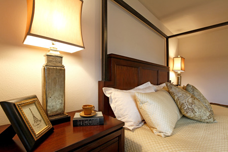 nightstand: High posts bed with a beautiful beige bedding and nightstand. Close up view from the corner