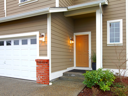 house siding: VIew ot the entrance orange door and garage form a walkway Stock Photo