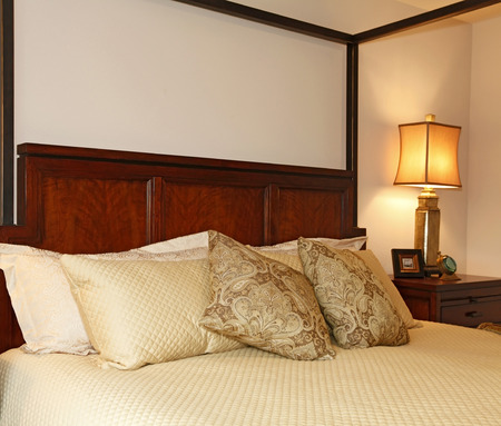 Cherry wooden bed. Close up view of warm beautiful bedding.