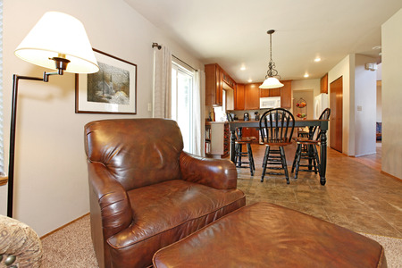 dining table and chairs: Living room with a leather chairs. View of the kitchen and dining table set