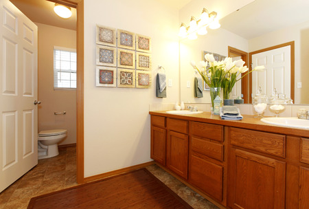 Bright bathroom with a brown rug and bright wooden cabinets. Decorated with fresh flowers and wall art. View of the toilet photo