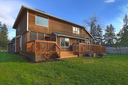 wood deck: Back of the cedar house with deck and a green lawn Stock Photo