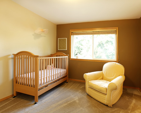 Baby room with crib and yellow chair and brown walls. photo