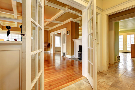 restoration: Hallway with an open door to a living room with an antique stove and chest.