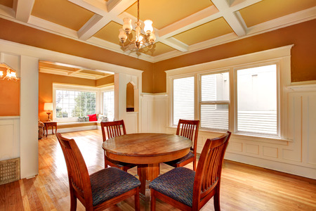 Bright dining room with a coffered yellow and white ceiling, hardwood floor. View of the living room photo