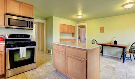 black appliances: Menta fresca sala cucina con elettrodomestici in acciaio e nero, armadi marrone chiaro. Vista della sala da pranzo
