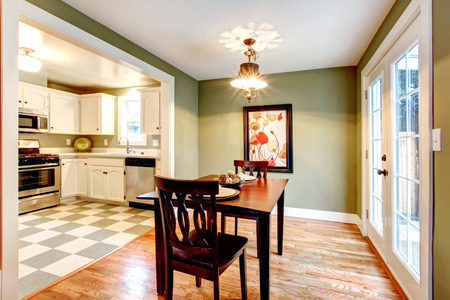 Small dining room with a hardwood floor and olive walls. Furnished with a black dining table set. View of the kitchen. photo