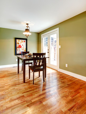 Small dining room with a hardwood floor and olive walls. Furnished with a black dining table set. photo
