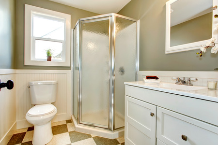 Bright bathroom with window. Olive walls blend perfectly with white cabinets, white toilet and glass door shower