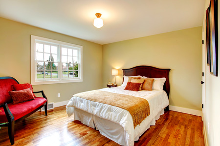 Light olive bedroom with hardwood floor and white french window. Furnished with a bed and an antique red settee