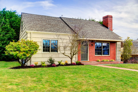One story siding house with tile roof and brick trim. View of the front exterior , walk way and green lawn6`