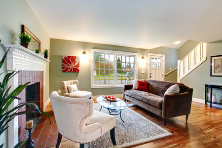Refreshing living room with light green walls, hardwood floor and white ceiling. Furnished with brown sofa, chairs and glass coffee table. Stock Photo