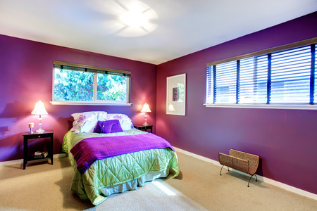 Elegant bedroom with beige carpet floor and contrast color bright purple walls. Green and purple bedding blend perfectly with red wall photo