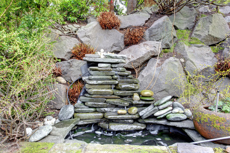 Beautiful small fountain with rocks. Great landscaping idea for a backyard garden