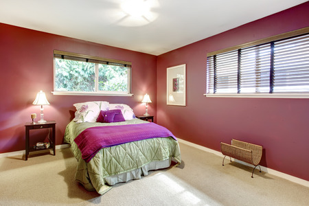 Elegant bedroom with beige carpet floor and contrast color bright red walls. Green and purple bedding blend perfectly with red wall photo