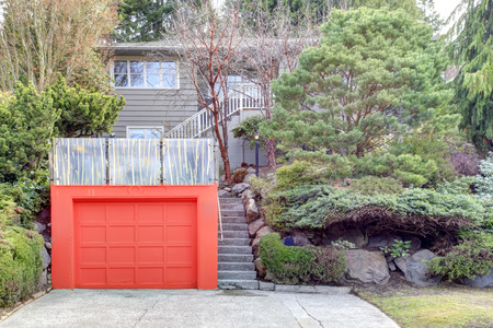 Clapboard siding house on a hill. Red door garage with roof top deck over it photo