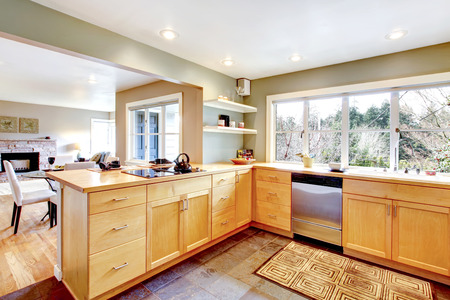 Kitchen with concrete floor and french window. Maple cabinets blend perfectly with light green wall. View of the dining and living room photo