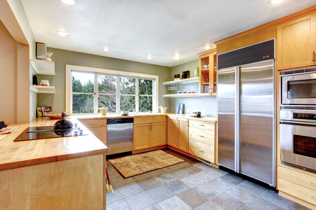 appliances: Kitchen with concrete floor and french window. Maple cabinets blend perfectly with stainless steel appliances Stock Photo