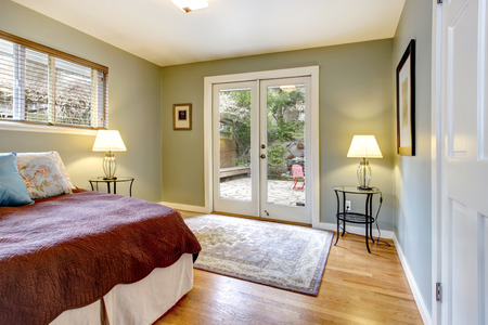 Olive walls cozy bedroom with hardwood floor and glass doors. View of the walkout deck photo