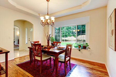 family rooms: Beautiful coffered ceiling dining room with a hardwood floor and french window. Furnished with a served dining table set. Stock Photo