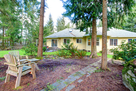 curb appeal: Beautiful backyard with green lawn and rest outdoor area with two wooden chairs.