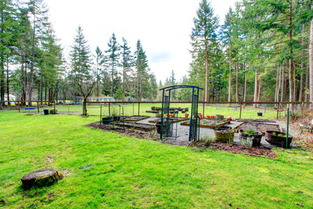 fenced: Green backyard with a fenced garden bed. Stock Photo