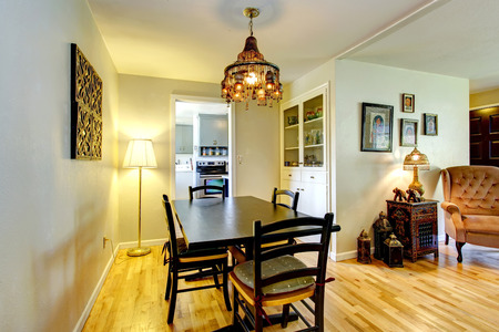 Bright dining area with hardwood floor, black table set and built-in cabinet photo