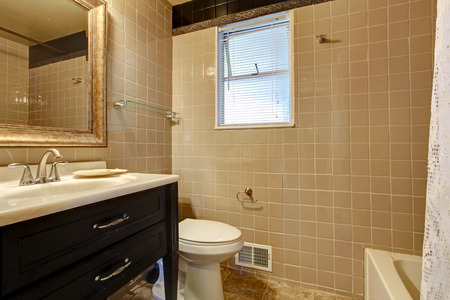 Tile wall bathroom with a concrete floor. Black wooden washbasin cabinet with a white sink photo