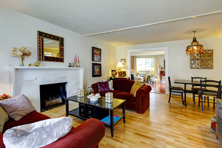 family rooms: White living room with a brick background fireplace, black coffee table and burgundy love seats. View of the dining area Stock Photo