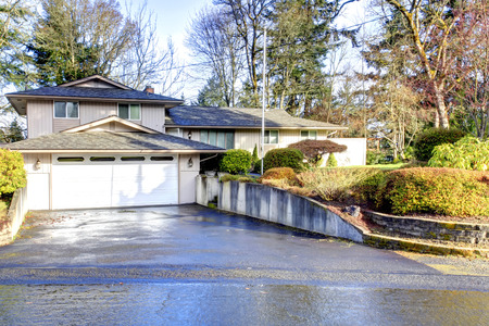 Big siding house with beautiful landscaping. View of the wet drive way photo