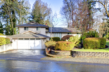 Big siding house with beautiful landscaping. View of the wet drive way and curb appeal photo